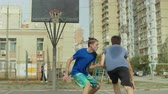 drible : Teenage streetball players playing one on one game on basketball court on street. Baskeball player dribbling and scoring points after layup shot while playing streetball together with friend outdoors.