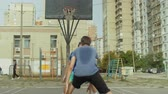 bodování : Sporty teenage friends playing one on one streetball game on basketball court on city street. Male basketball player taking a jump shot with resistance of defender and failed to score points outdoors