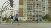 drible : Teenage streetball player dribbling and taking field goal shot while playing basketball game together with friend on street court. Basketball players playing one on one streetball game outdoors.
