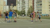 bodování : Teenage sporty basketball player dribbling and passing the ball to his teammate while playing streetball on court. Streetball player scoring points in the paint with layup shot during basketball game. Dostupné videozáznamy