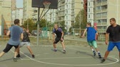basketball : Teeange sporty streetball team making pick and roll play while playing game on outdoor basketball court. Offensive player setting screen for teammate and moving towards the basket to receive a pass.