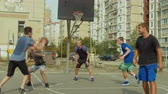 abroncs : Teenage basketball forward setting a screen on defender and receiving a pass from teammate, taking easy layup shot during streetball game. Streetball team making successful pick and roll play on court