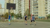 přestupek : Offensive streetball team making passes and scoring points in the paint with layup shot while playing game on basketball court. Basketball player making successful assist to his teammate during match.