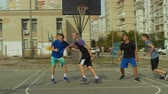 abroncs : Active sporty teenage friends spending great time playing basketball on outdoor court. Healthy lifestyle young men practicing streetball game on basketball court. Slow motion.