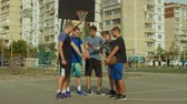 abroncs : Teenage basketball team stacking hands on court before starting playing streetball game. Team of streetball playing making pile of hands, showing unity and willing to win basketball match outdoors.