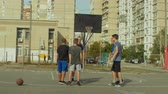 respeito : Teenage streetball players congratulating each other and shaking hands after basketball match on outdoor court. Cheerful basketball players showing respect to each other for fair competition outdoors. Stock Footage