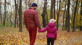 parentalidade : Positive chatting handsome father and cute little daughter holding hands taking a promenade in park alley on warm autumn day. Happy dad and elementary age girl relaxing in autumn nature during a walk. Stock Footage