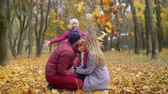 tossing : Beautiful parents sitting squatted, kissing tenderly in autumn park while adorable elementary age daughter throwing colorful autumn foliage over them. Happy family relaxing outdoors in fall season. Stock Footage