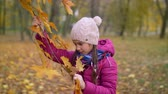arranjando : Positive cheerful cute elementary age girl in warm clothes holding branch of maple tree and tearing yellow leaves while collecting bouquet of autumn foliage in public park in fall season.