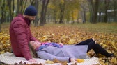 nostaljik : Affectionate couple in love cherishing every moments together and bonding while relaxing on picnic blanket in autumn nature. Chatting couple enjoying leisure on romantic day in indian summer.