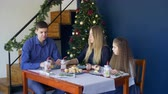 mason jar : Happy relaxed family and cute elemenatry age daughter having christmas dinner, eating cookies , drinking hot chocolate drinks from mason jars while celebrating winter holidays in home interior. Stock Footage