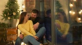 atmosférico : Smiling attractive couple in love sitting on windowsill and communicating while spending great time together in illuminated loft room. Couple relaxing together in domestic interior in the evening. Stock Footage