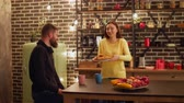 rogalik : Happy smiling woman serving coffee and croissants on kitchen table while attractive couple having snack together after work in the evening. Loving couple enjoying time together in domestic kitchen. Wideo