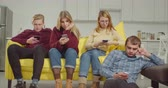 ignorer : Indifferent teenage friends spending leisure in domestic room, obsessed addicted with smart phones ignoring each other. Attractive teenagers phubbing each other, networking online on cellphone at home Vidéos Libres De Droits