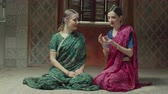 conquered : Conquered by aroma women sniffing wonderful flavor of dry perfume while sitting on floor at home. Charming females in traditional indian sari and jewelry one by one applying sachet with great pleasure Stock Footage