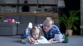 diligence : Adorable preschool girl diligently writing letters on notebook with pen during preschool home education in cozy domestic interior. Caring father holding daughters hand helping correctly writing.