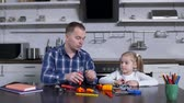 плоскогубцы : Caring father with toy set explaining to little girl use of different work tools while sitting at table in domestic kitchen during shop class. Dad teaching kid handling with tools at home craft lesson Стоковые видеозаписи