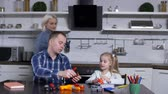 tightening : Father teaching tooling elementary school daughter, showing on toy tool kit tightening screw on bolt while loving mom joining then during shop class in domestic kitchen . Time to finish home schooling Stock Footage