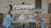 сумма : Two women friends with preteen kids enjoying drinks and fast food sitting at cafereria table while waitress bringing bill. Blonde female wondering at big bill while reading total amount to be paid. Стоковые видеозаписи