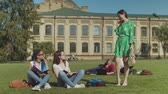 dominating : Multi ethnic university friends in glasses studying with notepads outdoor while sitting on campus lawn and mocking at older classmate not so smart. Sad woman being bullied going away in tears. Stock Footage