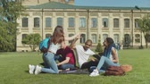 mnohonárodnostní : Group of positive diverse students greeting female friend giving five while sitting on green grass and preparing for university studies. Young multinational classmates studying outdoor on campus lawn.