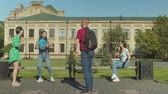 dominating : Multi ethnic college students mocking at girl in glasses picking up her backpack and throwing it in university campus. Young male standing up for upset friend sitting alone on bench and studying. Stock Footage