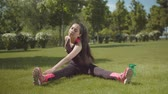 kas inşa : Chinese female athlete doing sport exercise on lateral muscles of back and abdominals sitting on green grass in city park. Sporty long haired asian fit woman training outdoors during intense workout.