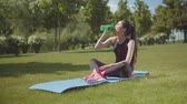 dedicação : Sporty female having energy drink during fitness workout on green park lawn. Young chinese woman sitting on fitness mat in city park and taking break from sport exercises to drink, active lifestyle.