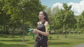 raffreddamento : Thirsty asian female athlete sipping energy drink while jogging and listening to music on smartphone in armband in green city park. Fitness woman taking break to drink during outdoor cardio training. Filmati Stock