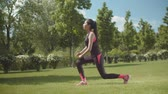 lunges : Asian sporty female doing lunges exercises for muscles of legs and buttocks in city park. Young long haired athletic female in sportswear training glutes outdoors, body care, sport lifestyle concept. Stock Footage