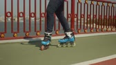 inline : Close-up of female roller feet skillfully rollerblading backwards crisscross, crossover and slide on river footbridge. Young woman in roller skates showing skill of riding over cityscape background.