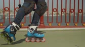 inline : Close-up of skillful womans legs in roller skates and knee pads doing cross position riding backwards and forwards crisscross along city river bridge footpath. Active woman rollerskating outdoors. Stock Footage