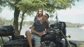 Carefree young couple enjoying summer leisure on motorcycle in public park. Laughing playful cute teenage girl embracing handsome boyfriend sitting on custom motorbike in nature during moto trip.