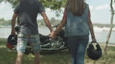 всадник : Rear view of young motorbiker couple with helmets holding hands walking towards custom motorcycle before journey over cityscape background. Positive riders ready for summer roadtrip on motorbike. Стоковые видеозаписи