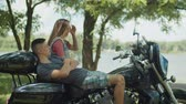 Positive relaxed young couple communicating, enjoying summer vacation trip on motorcycle and spending great time together outdoors. Carefree moto trip riders relaxing on motorbike and talking. Stock Footage