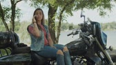 Stunning motorbiker girl with long hair chatting on smartphone while sitting on motorcycle in summer nature. Carefree pretty young female talking on phone while resting on motorbike in countryside. Stockvideo