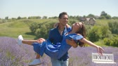 lavanda : Carefree african american man carrying his beloved pretty woman on hands and spinning around in lavender field. Positive playful mixed race couple in love enjoying summer vacations in countryside. Stock Footage