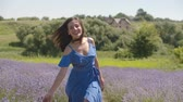 Smiling long hair brunette woman in stylish dress running her hand gently over fragrant lavender blossoms on sunny day. Charming young female touching softly lavender shrubs during a walk on field.