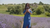 koku : Charming carefree young female in elegant blue dress smelling fresh fragrant lavender blosooms while walking through lavender field. Pretty cheerful woman enjoying unity with nature in countryside. Stok Video