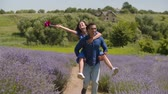 Excited african american man giving piggyback ride to joyful woman with pinwheel and running through lavender bushes. Carefree playful mixed race couple having fun in summer nature in countryside.