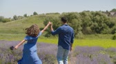 Positive smiling african american man with carefree attractive woman holding bouquet of fresh lavender blossoms having fun, while walking in blooming field during summer vacations in countryside.