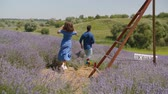 Rear view of carefree joyful multiethnic couple running in lavender field, enjoying freedom and active lifestyle over beautiful nature background. Excited people relaxing in rural field on sunny day.