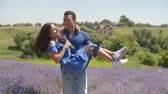 Affectionate handsome african american man carrying charming woman with bouquet of fresh lavender flowers in his arms during a walk in lavender field. Loving mixed race couple enjoying outdoor leisure