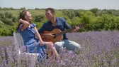 Romantic affectionate african american man playing acoustic guitar, singing love song to his charming woman while multi ethnic couple enjoying closeness and summer outdoor leisure in lavender field Stockvideo