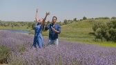 Joyful african american guy blowing soap bubbles and excited pretty woman trying to catch them in lavender field. Carefree multiracial couple enjoying freedom and outdoor leisure in countryside.