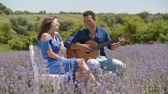 Loving african american man playing acoustic guitar and singing love song to pretty woman in lavender field. Positive mixed race couple playing guitar while enjoying romantic date in summer nature