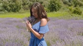 臭い : Carefree charming brunette female in blue dress enjoying fragrant of blooming lavender flowers in summer nature. Positive pretty woman holding bouquet of fresh lavender blossoms and inhaling aroma.