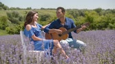 Romantic handsome dark-skinned man serenading his charming beloved woman with acoustic guitar in lavender field. Affectionate mixed race couple playing guitar on romantic date in summer nature.