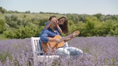 Romantic handsome black guy playing acoustic guitar while playful stunning woman embracing from behind and covering his eyes with hands in lavender field, expressing love, happiness and joy.
