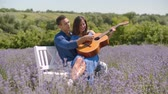 Excited happy multiracial couple in love enjoying freedom, outdoor leisure and closeness while relaxing with acoustic guitar in fragrant lavender blossoms, expressing positivity, carefree mood and joy
